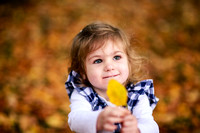 little girl holding up a yellow leaf in the fall